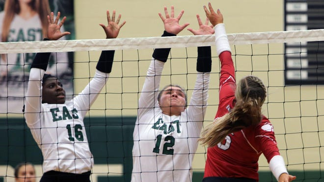 East Henderson's Sontee Moore (16) and Cami Bailey (12) go up for the block against Hendersonville's Chloe Conroy during last year's match at East.