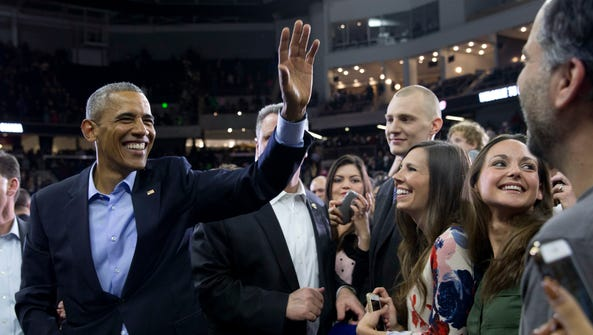 President Obama waves as he greets people in the audience