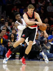 Portland Trail Blazers' Meyers Leonard, right, loses control of the ball due to Philadelphia 76ers' Nerlens Noel, left, during the first half of an NBA basketball game, Saturday, Jan. 16, 2016, in Philadelphia.