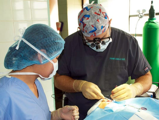 Doctor Frank Angullo operates on a patient during a