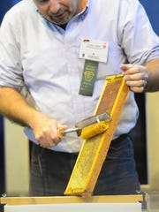 Gary Carns uses an electric uncapping knife to get