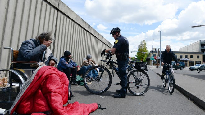 Salem Police Officer Pat McDermott of the Downtown Enforcement Team speaks with homeless men and women gathered near the Center Street Bridge on Wednesday, May 6, in downtown Salem.
