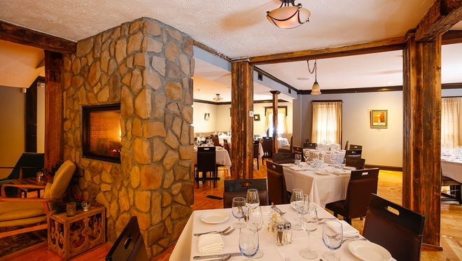 The dining room is softly lit with a low ceiling, glossy wooden floors, central fireplace and comfy chairs.