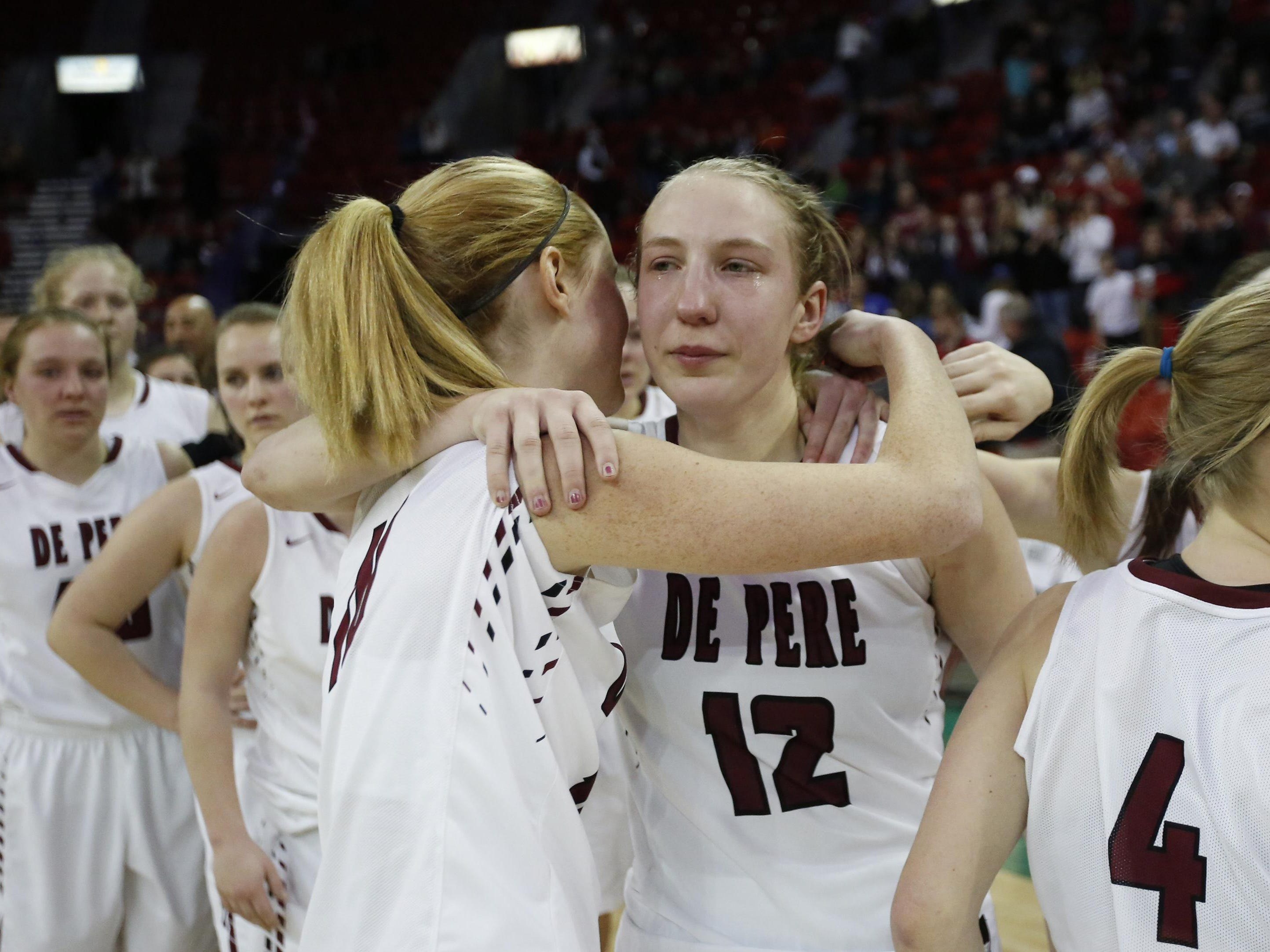 De Pere's Lizzie Miller hugs teammate Lauren DeMille after their loss to Appleton North High in the WIAA Division 1 State Tournament girls basketball championship game Saturday at the Resch Center in Ashwaubenon. See more photos from the game at greenbaypressgazette.com.
