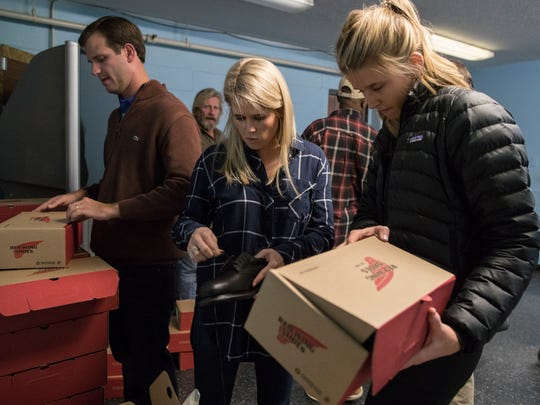 Alex Currie, from left, Kari Currie and Candace Quill hand out boxes of shoes at the Healing Place recovery facility in downtown Louisville during the Hearts to Soles event. Nov. 22, 2017