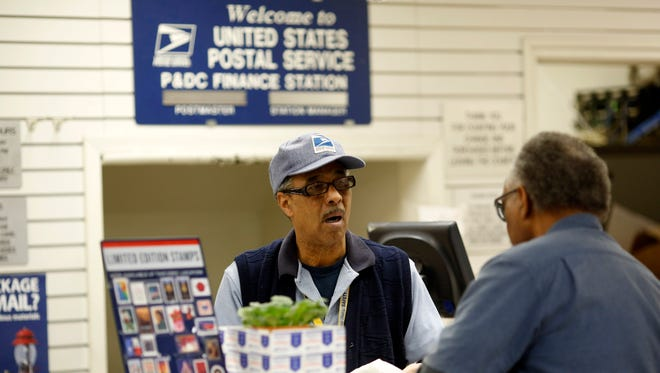An United States Postal Office employee helps a customer at the post office on Evans Street in San Francisco in December.