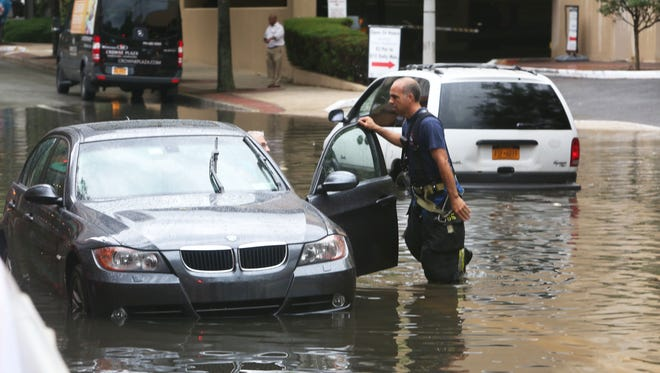 White Plains firefighters check on the occupants of three cars that were stranded by rising flood waters on Hale Avenue near Maple Avenue in White Plains July 15, 2014. Heavy rains swept across the region causing several roads to flood.