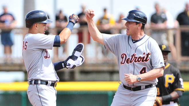 Michigan football coach Jim Harbaugh congratulates Tigers' Jose Iglesias after his single in the first inning.