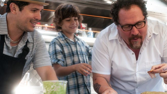 "John Leguizamo, Emjay Anthony, and Jon Favreau in a scene from the movie ""Chef."""