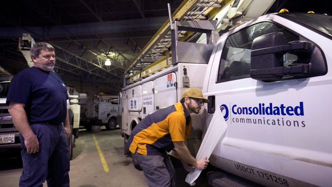 In this Friday, Jan. 12, 2018, photo, Chris Bagley of Sebago Signworks pulls off the covering of a new Consolidated Communications logo he applied to the door of a former FairPoint truck as fleet mechanic Steve Morin looks on in Portland, Maine. Consolidated Communications bought FairPoint Communications and is discarding the old name and making plans to upgrade service of tens of thousands of customers in northern New England.