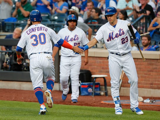 New York Mets' Michael Conforto (30) is congratulated by Matt den Dekker after scoring against the Washington Nationals during the first inning of a baseball game, Friday, July 13, 2018, in New York.