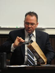 Bureau of Criminal Investigation Special Agent Perry Roeser pulls evidence collected at the scene out of an evidence bag during testimony in day four of the Joel Jenkins trial Thursday in Pike County Common Pleas Court.