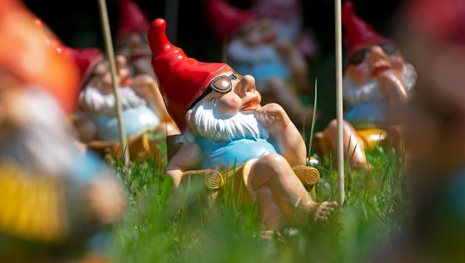 A dwarf figure sits in the sun in Germany's Garden Gnom Park (Zwergen-Park) in Trusetal, Germany, Sunday, April 22, 2018. Every year up to 100,000 tourists visit the Garden Gnome Theme Park with more than 2,500 garden gnomes.