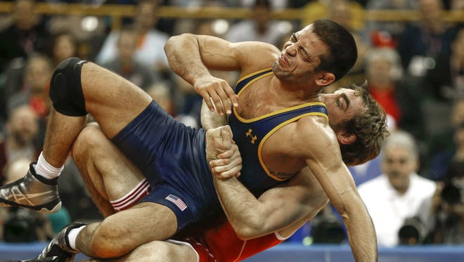 Daniel Dennis, right, scores quick gut wrench points to score an Olympics-qualifying win over Tony Ramos on Sunday during the Olympic Wrest;omg Trials at Carver-Hawkeye Arena in Iowa City, Iowa.