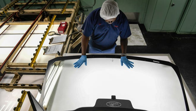 Pre-processing technician Mel Motley checks over the windshield for paint and defects July 25, 2017, at Carlex Glass Co. in Nashville. The state and local governments provided Carlex millions in incentives.