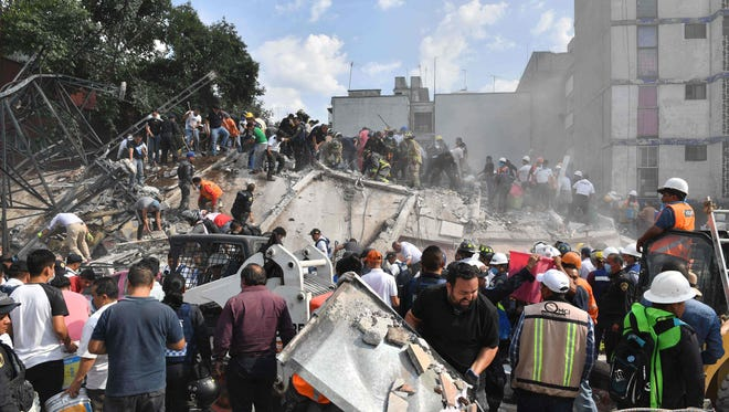 Rescue workers and volunteers in Mexico City are pictured removing rubble from a flattened building in search of survivors following the massive magnitude-7.1 earthquake  that hit the Mexican capital.