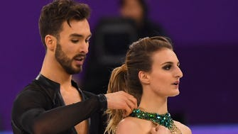 Gabriella Papadakis, right, and her ice dancing partner, Guillaume Cizeron, tend to her dress after a wardrobe malfunction.