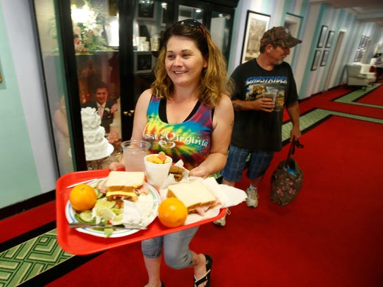 Amy Eggleston carries a tray of food as she and Jarrod
