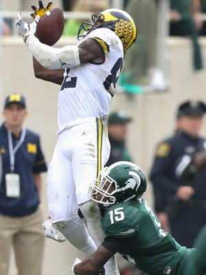 Michigan's Amara Darboh pulls in a catch over MSU's Tyson Smith. Darboh finished with eight catches for 165 yards.