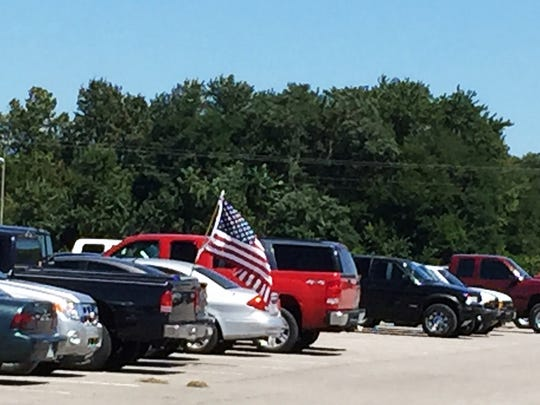 Five American flags waved from vehicles parking at