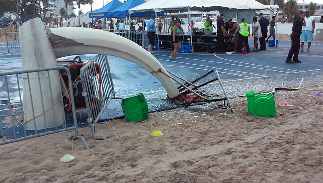 Glass is scattered around a toppled basketball hoop after a waterspout made landfall at Fort Lauderdale Beach, Fla. on Monday. Authorities say three children were injured when the waterspout uprooted a bounce house and sent it across a parking lot into the road.