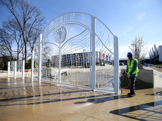 Clifford Jones hoses down the front entrance area where 16-foot-wide powder coated iron gate that will welcome guests as finishing touches are put on Elvis Presley's Memphis ahead of Thursday's grand opening.