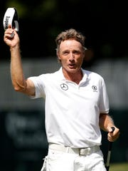 Bernhard Langer waves to the gallery after making a