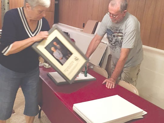 Bonnie and Jack Rocco of Coldwater are shown working on the clean-up and restoration of over 200 photos of past inductees into the Michigan Farmers' Hall of Fame.