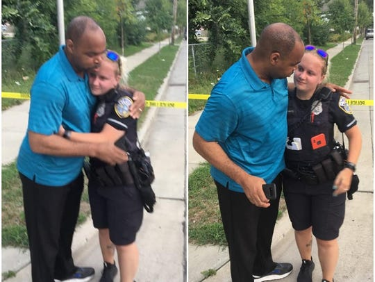 Community activist Tracey Dent hugs a police officer