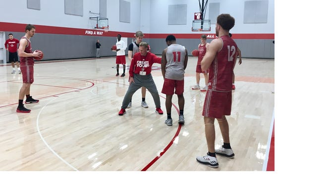 South Dakota men's basketball coach Todd Lee demonstrates a drill for his players at a workout on Thursday afternoon at the Sanford Coyote Sports Center.