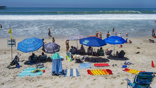 With most of Southern California's coastline is shut down for the Fourth of July holiday due to a spike in coronavirus cases, the beach in San Clemente remains open as crowds, socially distanced, fill the sand even with high surf, on Saturday, July 4, 2020, in San Clemente.