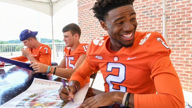 Clemson quarterback Kelly Bryant, right, quarterback Hunter Johnson, middle, and quarterback Chase Brice, left, sign autographs during fan day at Memorial Stadium in Clemson on Sunday.