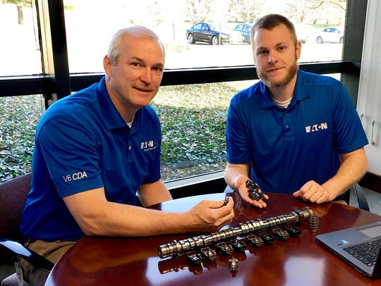 Jim McCarthy, left, chief engineer, vehicle technologies and innovation, Eaton's Vehicle Group, and Eaton co-op student Jeff Brown, Western Michigan University, examine a cam shaft and rollers and sliders in Eaton's Galesburg facility on May 1, 2018. McCarthy and Brown are conducting research on the use of rollers, sliders and a combination of the two to reduce friction and improve fuel efficiency of gasoline engines for passenger vehicles.