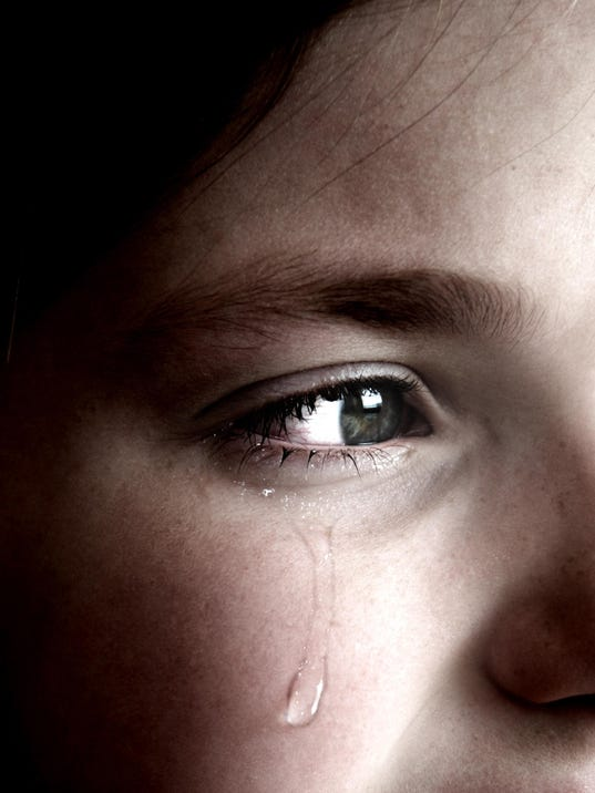 Crying girl with tear on cheek