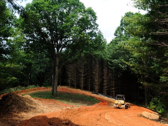 Construction crews work on the new road that was rerouted around an old oak tree to preserve its place on the former Coggins Farm property. The property will become a 99-lot community called Sovereign Oaks.