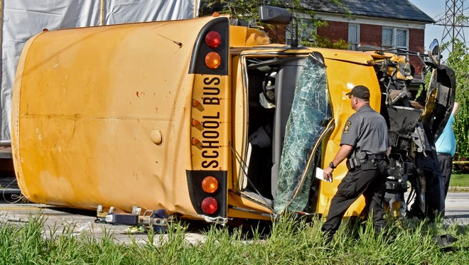 A Pennsylvania State Police trooper looks over a school bus that overturned after a collision in East Lampeter Township, Pa., Wednesday, May 17, 2017. Authorities say the school bus flipped on its side in a hit-and-run accident in eastern Pennsylvania, sending more than a dozen people to the hospital, including two students with trauma injuries. Police were seeking a light-colored sedan involved in the crash that sped away. (Blaine Shahan/LNP via AP)