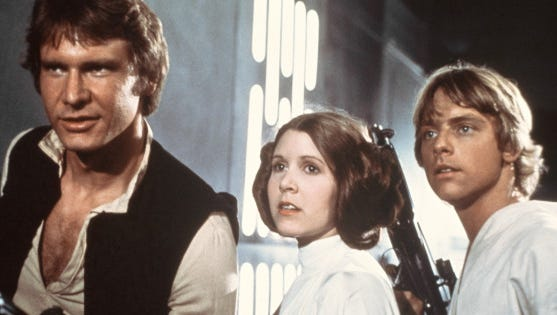 """This 1977 file image provided by 20th Century-Fox Film Corporation shows, from left, Harrison Ford, Carrie Fisher, and Mark Hamill in a scene from """"Star Wars"""" movie released by 20th Century-Fox in 1977."""