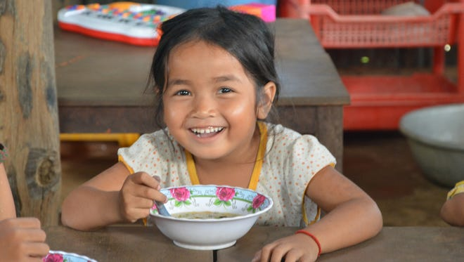 A Cambodian girl eats a meal in her village.