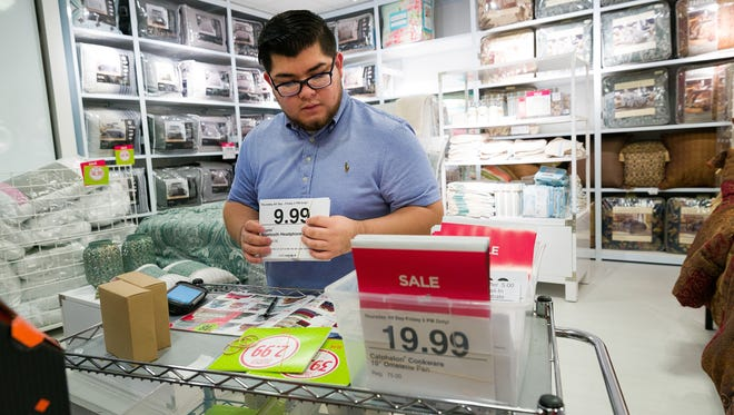 Angel Chavez, a pricing associate at J.C. Penney, prepares bedding inventory for Black Friday sales at the department store's Coastland Center mall location in Naples on Monday, Nov. 21, 2016.