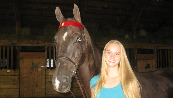 Johnston volleyball player Kristen Stucker, right, pictured with Dexter, one of her three horses boarded at Heartland Stables in Grimes, has used her focus honed in showing horses while on the volleyball court.