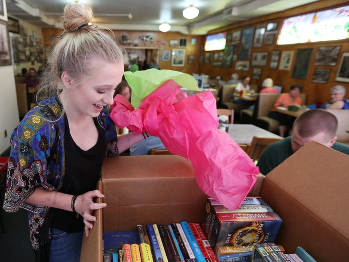 Abby Armstrong reacts as she opens a box full of books