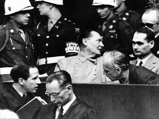 Nazi German Foreign Minister Joachim von Ribbentrop, right, leans in front of Rudolf Hess, Hitler's deputy, to confer with his lawyer, lower left, while Hermann Goering, center, chief of the German air force and one of Hitler's closest aides, turns to talks with Karl Doenitz, rear right, during the Nuremberg war crime trial session on March 27, 1946. Stephen Pedro of Great Falls identified himself in the photo as the guard at the far left.