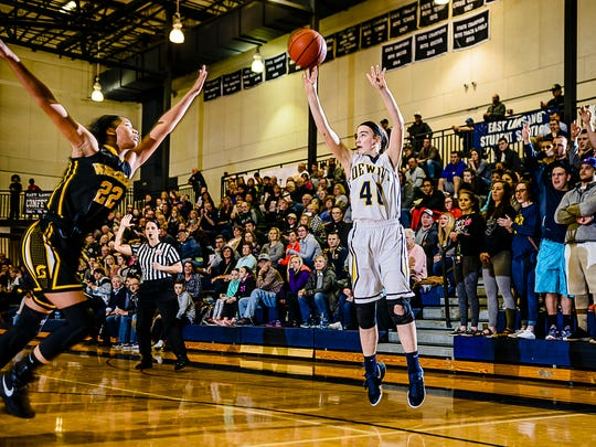 Madison Petersen,right, of DeWitt lines up a 3-point shot over Alicia Smith of Waverly during their game Monday February 27, 2017 at East Lansing High School.  KEVIN W. FOWLER PHOTO