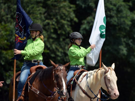 Cassidy Latchaw, left, riding Annie, and Noelle Moody riding Sugar, prep their flags for the start of teh Wellsville Boots & Saddles Drill Team demo the 40th annual York County 4-H Fair, Sunday, August 13, 2017.  John A. Pavoncello photo