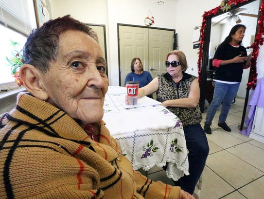 Resident Alicia Guzman, foreground, sits in the living