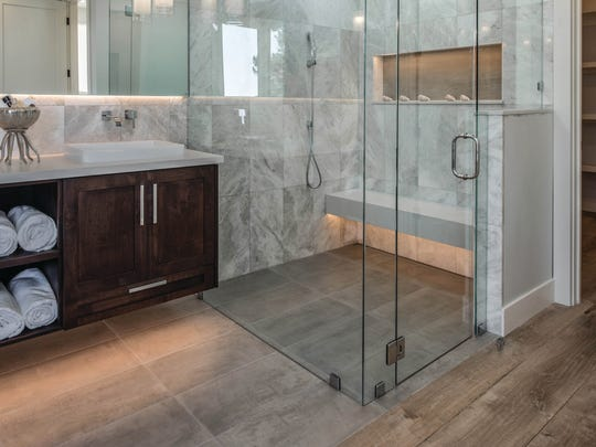 The shower is curbless to prevent tripping, the bench and floor are heated, and the linear drain is beneath the bench.