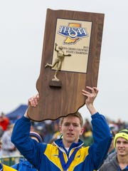 Carmel's Teddy Browning hoists the trophy over his