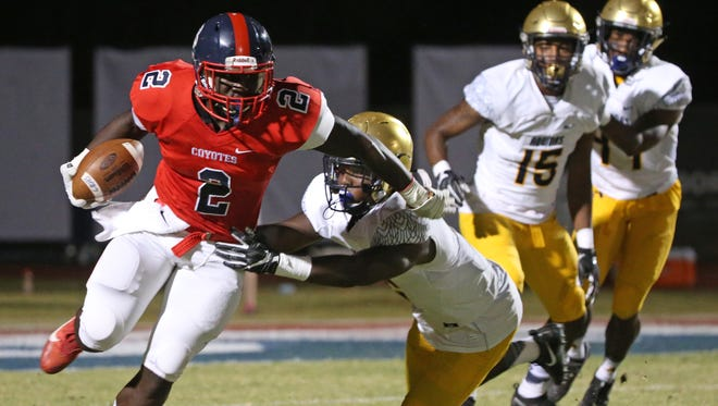 Centennial's Zidane Thomas (2) stiff arms St. Thomas Aquinas' Trenell Troutman (2) in the first half at Centennial High School in Peoria, Ariz. on Sept 29, 2017.