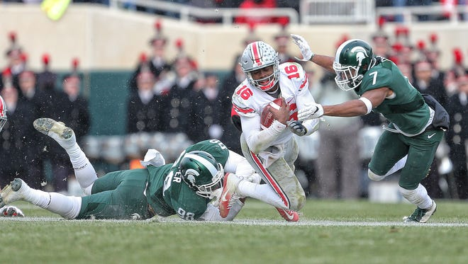 Nov 19, 2016; East Lansing, MI, USA;  Ohio State Buckeyes quarterback J.T. Barrett (16) is tripped up by Michigan State Spartans defensive end Demetrius Cooper (98) during the second half of  a game at Spartan Stadium.