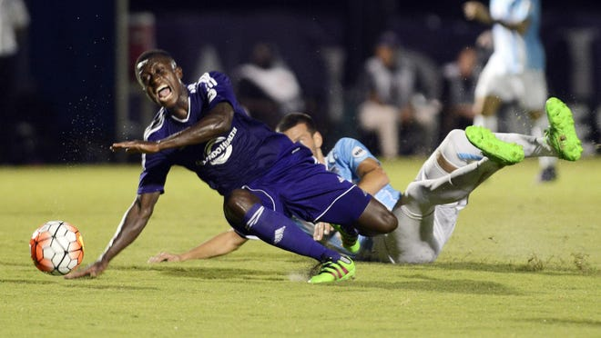 Richie Laryea of Orlando City B is tackled by Bruno Perone of Wilmington during their season opening game Saturday evening.